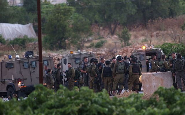 IDF soldiers assemble in the Palestinian village of Halhul, north of Hebron, after the bodies of three Israeli teenagers were found nearby, Monday, June 30, 2014 (photo credit: Nati Shohat/FLASH90)