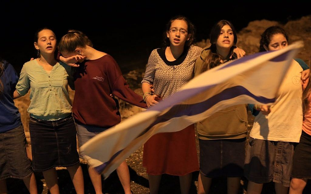 Young Israelis mourn near the Palestinian village of Halhul, on Monday night, after the bodies of three teenagers, Eyal Yifrach, Naftali Fraenkel and Gil-ad Shaar, were found in a field there. (Photo credit: Nati SHohat/FLASH90)