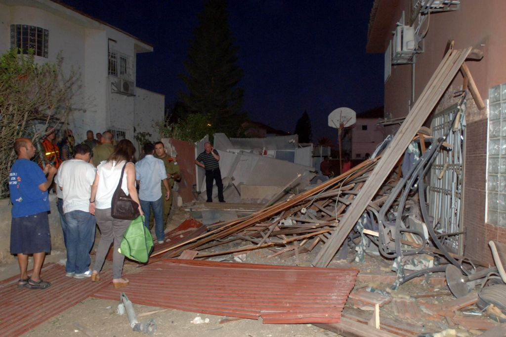 Israeli soldiers inspect rocket damage to a house in the southern city of Beersheba on Thursday, July 10, 2014 (photo credit: Flash90)