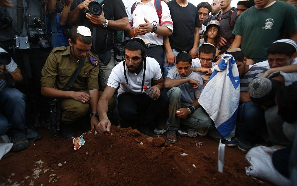 Men placing rocks on the grave of three slain teens. (photo credit: Yonatan Sindel/Flash90)