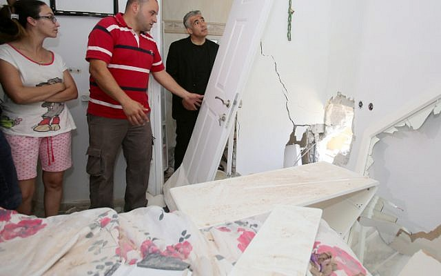 Finance Minister Yair Lapid (R) visits the Sderot home struck by rocket fire. July 03, 2014. (photo credit: Edi Israel/FLASH90)