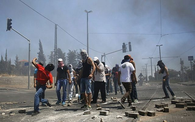 Masked Palestinian protesters throw stones towards Israeli police (unseen) during clashes in the Shuafat neighborhood in East Jerusalem, on July 3, 2014 (Photo credit: Sliman Khader/FLASH90)
