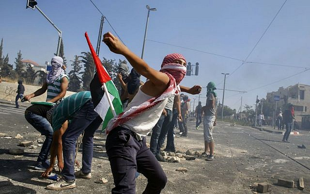 File photo of masked Palestinian protesters hurling stones at Israeli police during clashes in the Shuafat neighborhood in East Jerusalem, July 3, 2014. (photo credit: Sliman Khader/Flash90)