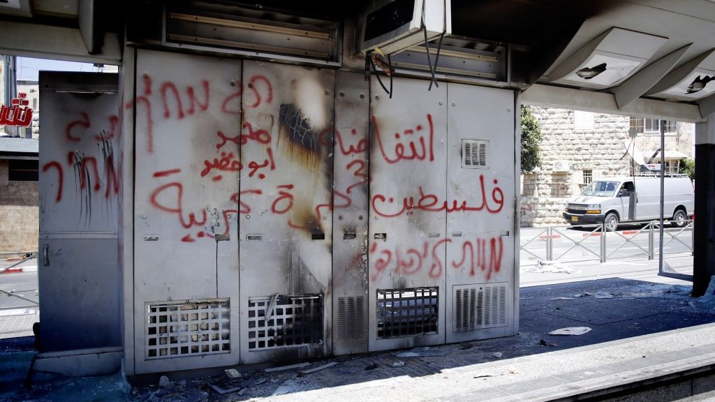 Graffiti reading 'Price Tag. Death to Jews' is seen spray-painted on what remains of a Light Rail station which has been vandalized by Palestinians in the Arab neighborhood of Shuafat, Jerusalem, July 2014. (photo credit: Sliman Khader/Flash90)