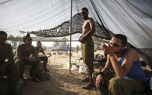 IDF soldiers seen in a tent in a field, near the Gaza border in Southern Israel, on Sunday, July 6, 2014 (photo credit: photo credit: Hadas Parush/Flash90)
