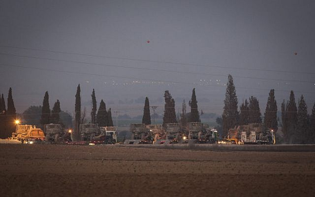 IDF APC's (Armed Personnel Carrier) are led on trucks through a field, near the Gaza border in Southern Israel, on July 6, 2014.  (photo credit: Hadas Parush/Flash90)