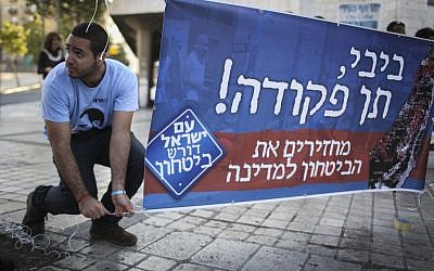 File: An activist with the right-wing Im Tirzu organization putting up a sign in Jerusalem calling on Benjamin Netanyahu to act to stop Gazan rocket fire, on Monday, July 7, 2014. (photo credit: Hadas Parush/Flash90)