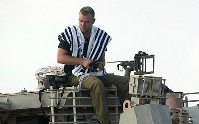An IDF soldier prays atop an armored IDF bulldozer near the Gaza border in southern Israel on the first day of Operation Protective Edge, July 8, 2014. (photo credit: David Buimovitch/Flash90)