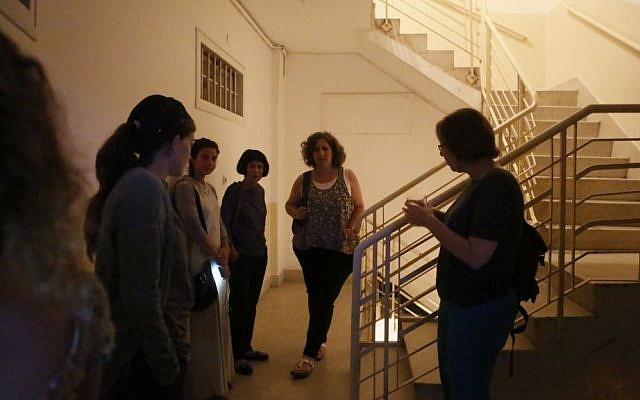 Israelis take cover in the hallway of an apartment building as a Code Red alert sound in Jerusalem, Tuesday, July 8, 2014. (photo credit: Miriam Alster/ Flash90)