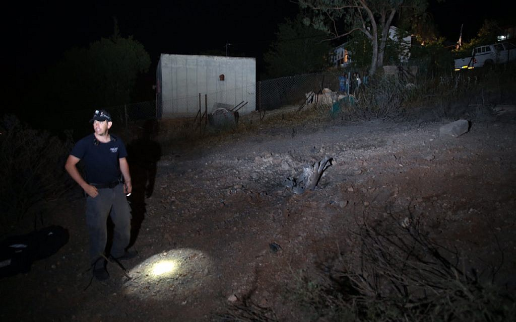 Israeli police inspect the site where a rocket fired by Palestinian militants from Gaza, hit in the area of Ramat Raziel, near Jerusalem. July 8, 2014. (photo credit: Nati Shohat/Flash90)