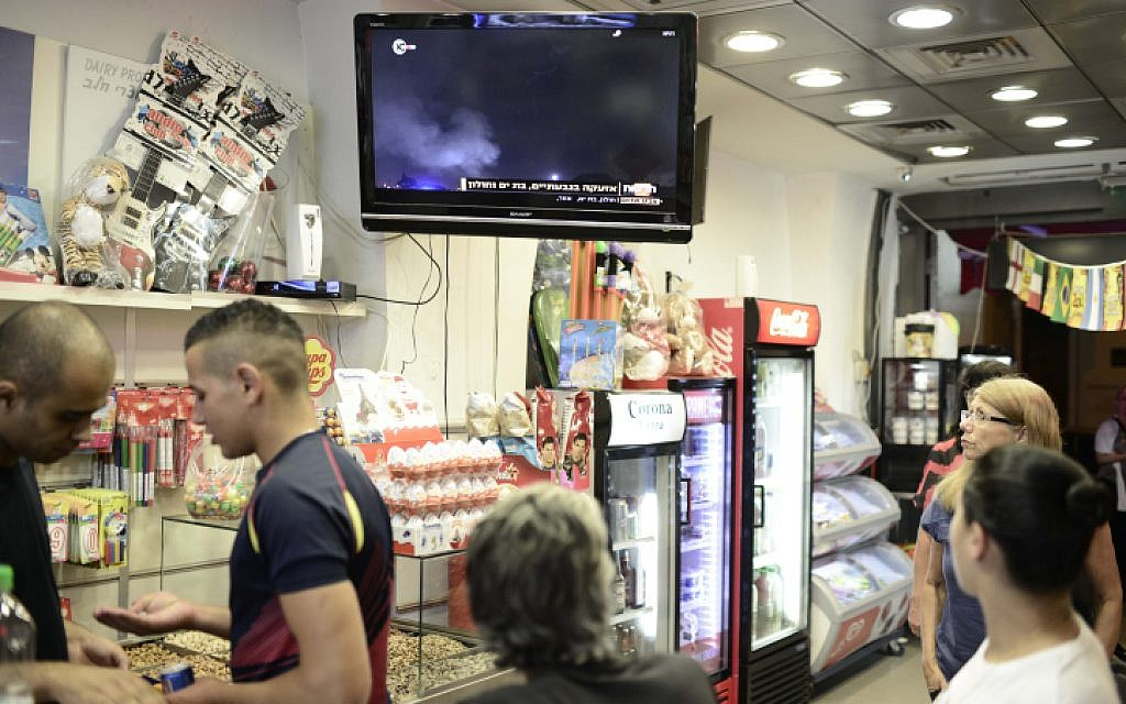Shoppers watch TV broadcasts about the offensive Israel launched against the Gaza Strip, with a series of airstrikes in response to increasing rocket attacks fired into Israel. July 08, 2014. (photo credit: Tomer Neuberg/Flash90)