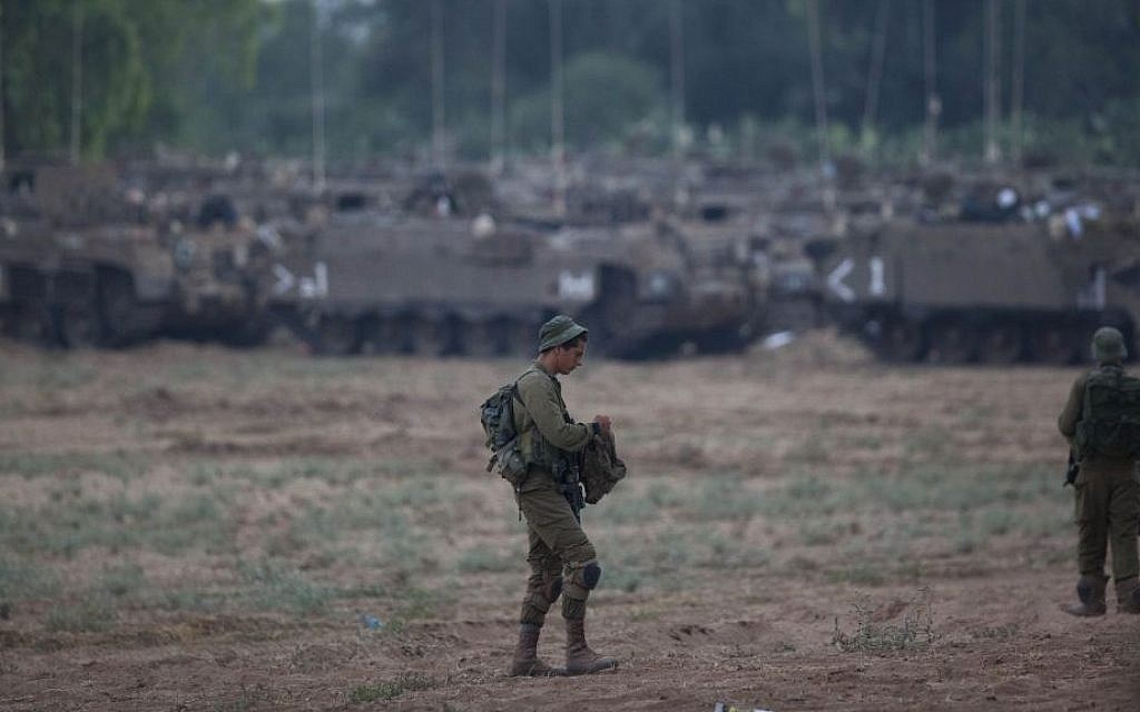 A soldier stands in a field near the Gaza border with IDF APCs (Armed Personnel Carriers) in the background, Wednesday, July 9, 2014. (photo credit: Yonatan Sindel/Flash90)