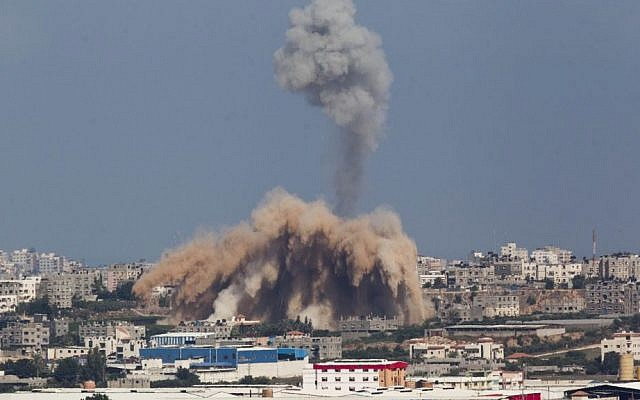 Smoke and debris rise after an Israeli airstrike on the Gaza Strip, as seen from the Israeli side of the Israel-Gaza border on the second day of Operation Protective Edge, Wednesday, July 9, 2014. (photo credit: Yonatan Sindel/Flash90)