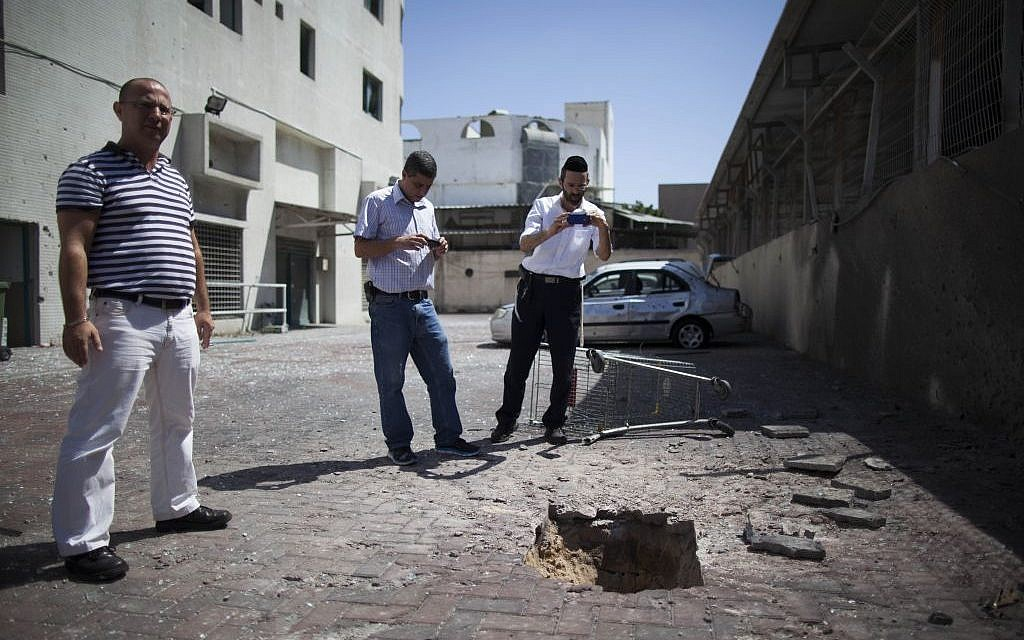 Israelis look at a crater caused by a rocket outside a shop in Ashdod, on the second day of Operation Protective Edge, Wednesday, July 9, 2014 (photo credit: Yonatan Sindel/Flash90)