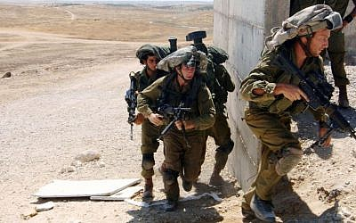 Israeli soldiers from the Paratroopers Brigade take part in a training exercise where they practice door-to-door combat in inhabited areas in Tze'elim, southern Israel, Thursday, July 10, 2014. (Flash90)