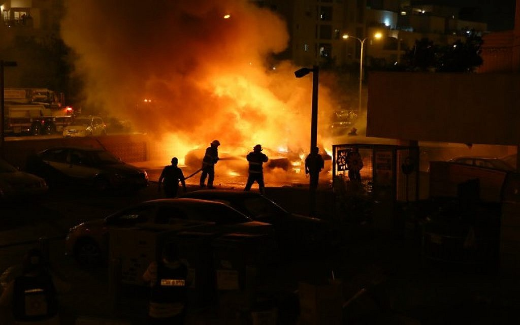 Fire fighters and police units were on the scene of an explosion in Ashdod caused by rocket fire from Gaza, on the third day of Operation Protective Edge, July 10, 2014. The rocket had landed on a car, crushing it, and causing the building's gas tank to explode and burst into flames. (Photo credit: Flash90)