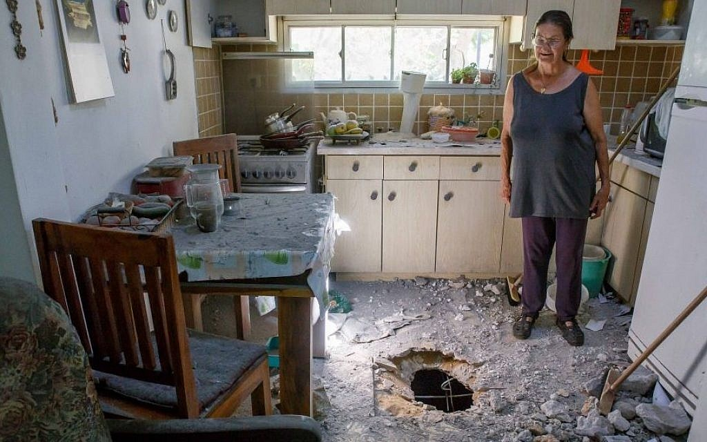 An Israeli woman surveys the damage caused to her parents' house in a community in southern Israel after it was hit by a rocket from Gaza,  July 11, 2014. (Photo credit: Flash90)
