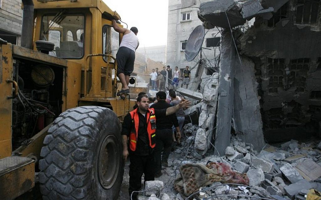 Palestinians remove the rubble of the Ghanam family home after it was targeted in an Israeli air raid on Rafah, in the southern of Gaza strip, on July 11, 2014. Five Palestinians, including a woman and seven-year-old child, died when the home of a Hamas operative was hit, Gaza emergency services said. (Photo credit: Abed Rahim Khatib/Flash90)