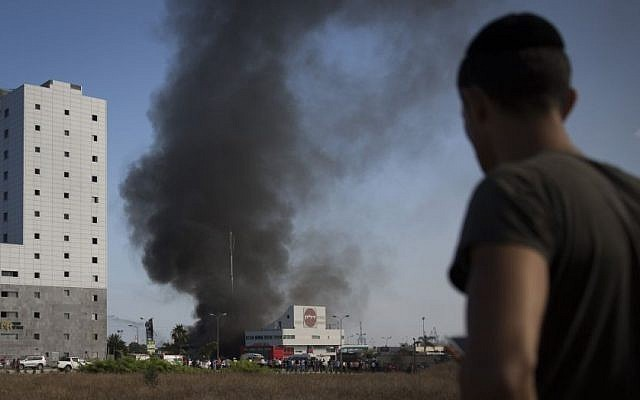 An Israeli watches smoke rise from a gas station in Ashdod that was hit directly by rocket fire from Gaza on the fourth day of Operation Protective Edge, Friday, July 11, 2014. (photo credit: Hadas Parush/Flash90)