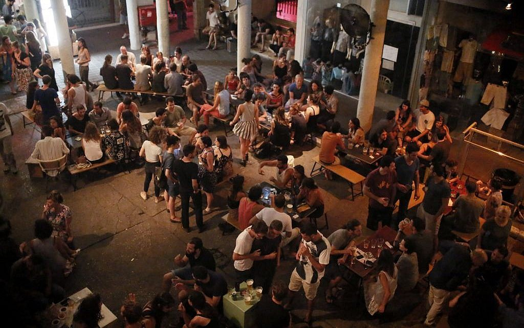 Israelis seen at a bar in Tel Aviv, central Israel. Several alarms sounded in the past few days warning about rockets fired from Gaza into Israel, and the Tel Aviv area. They were intercepted by the Iron Dome missile system. July 10, 2014. (photo credity: Miriam Alster/FLASH90)