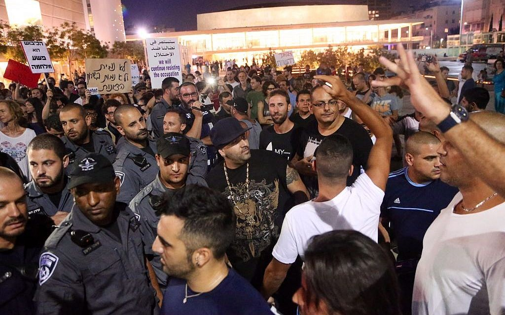 Groups of Israelis protest following an air raid siren warning of a rocket attack in Tel Aviv, on July 12, 2014. (Photo credit: FLASH90)