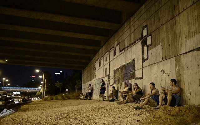 Israelis take cover as an alarm siren sounds, warning of incoming rockets in Tel Aviv, on the fifth day of Operation Protective Edge, Saturday, July 12, 2014 (photo credit: Tomer Neuberg/Flash90)