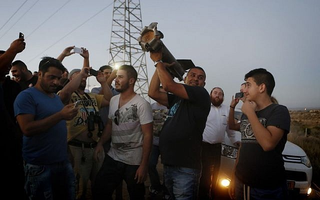 Residents of Sderot looking at a piece of a rocket that fell in an open field (photo credit: Miriam Alster/Flash 90)