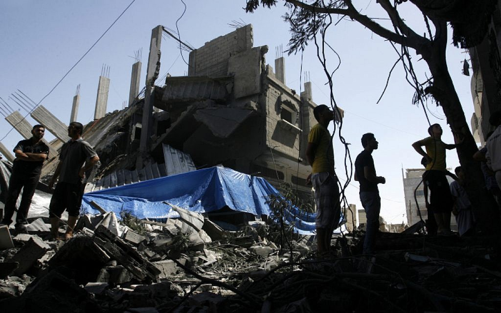 Palestinians seen walking among the rubble of a destroyed house following an Israeli missile strike, in Rafah on July 14, 2014. (photo credit: Abed Rahim Khatib/Flash90)