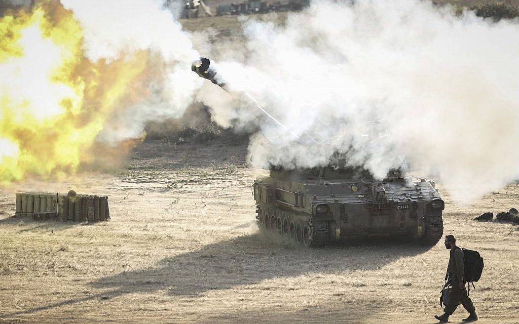 An Israeli soldier walks past an artillery cannon as it fires a shell to the Gaza Strip from a temporary base set up near the border, Monday, July 14, 2014 (photo credit: Hadas Parush/Flash90)