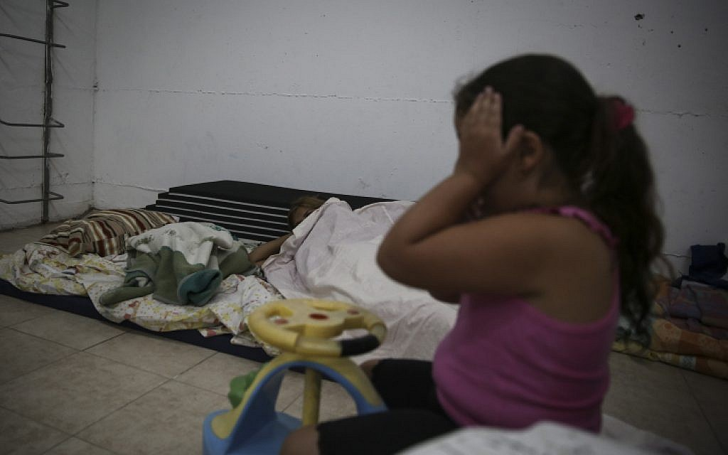 A girl sits in her building bomb shelter in the southern city of Ashkelon, July 14, 2014. (photo credit: Hadas Parush/Flash90)