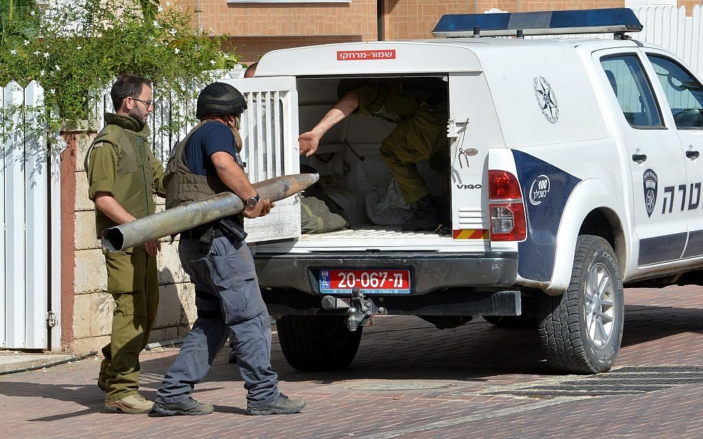 Israeli security carry away a missile, fired from Gaza into Israel, that landed in a yard in the Southern Israeli city of Ashkelon, Monday, July 14, 2014 (photo credit: FLASH90)