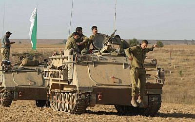 IDF soldiers seen near armored personnel carriers (APCs) by the southern Israeli border with Gaza, on the eighth day of Operation Protective Edge, July 15, 2014. (photo credit: Yossi Aloni/Flash90)