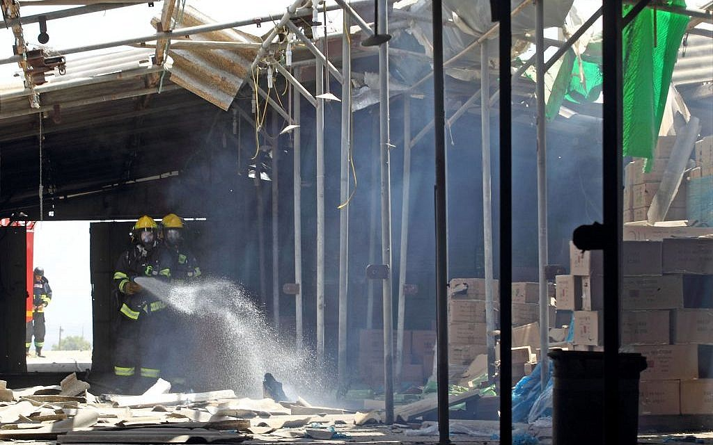 Firefighters extinguish a blaze caused when a rocket lobbed from Gaza struck kibbutz Nir Am in southern Israel on Tuesday, July 15, 2014 (photo credit: Yossi Aloni/FLASH90)