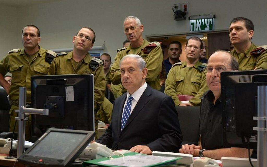 Prime Minister Benjamin Netanyahu with IDF chief Lt. Gen. Benny Gantz (standing directly behind him) and then-defense minister Moshe Ya'alon (seated right), monitoring IDF ground operations in Gaza during a meeting at the Kirya military headquarters in Tel Aviv on July 18, 2014. (Haim Zach/GPO/Flash90)