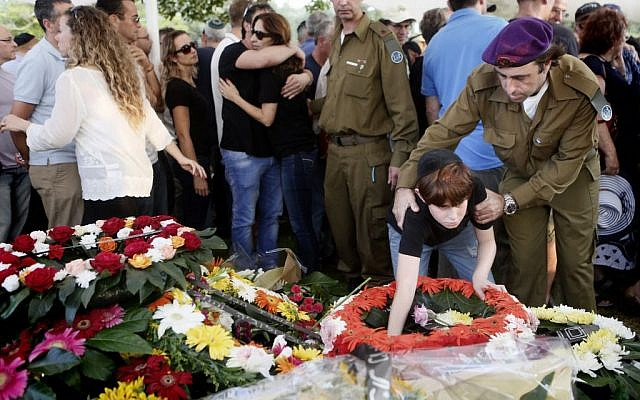 The son of IDF Major Amotz Greenberg (res.), 45, seen at the grave of his father during the funeral at the military cemetery in Hod HaSharon on Sunday, July 20, 2014. Greenberg was killed by Hamas terrorists who tunneled into Israel and opened fire on his army vehicle on July 19. (Photo credit: Miriam Alster/Flash90)