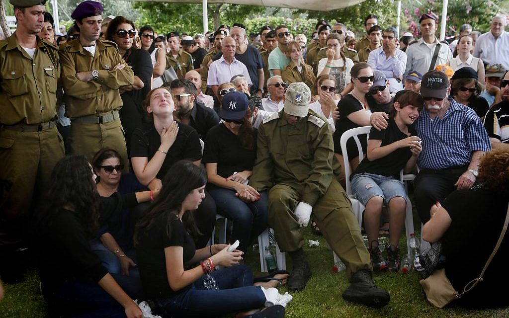 The family and friends of Major Amotz Greenberg (res.), 45, mourn during his funeral at the cemetery in Hod HaSharon on Sunday, July 20, 2014. Greenberg was killed by Hamas gunmen who tunneled into Israel and fired on his IDF jeep on July 19. (Photo credit: Miriam Alster/Flash90)