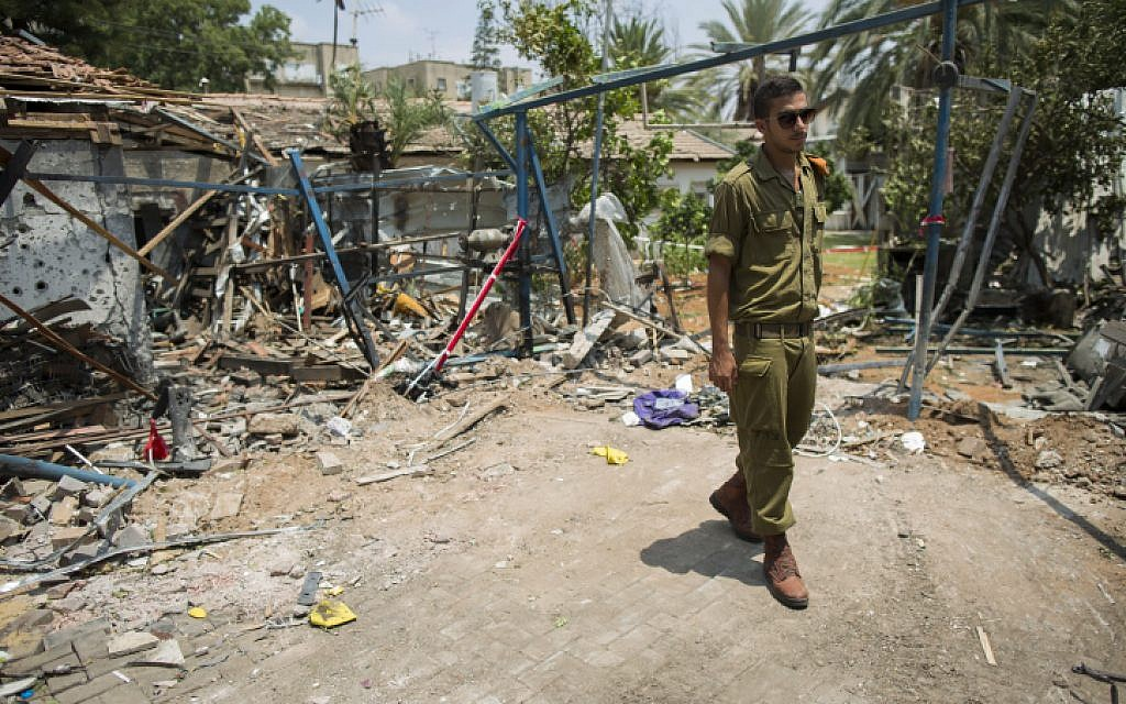 An Israeli soldier looks at the damage to a house following a rocket attack from the Gaza Strip on the town of Yehud, near Ben Gurion Airport, on July 22, 2014. (photo credit: Yonatan Sindel/Flash90)