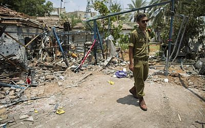 An Israeli soldier looks at the damage to a house following a rocket attack  from the Gaza Strip on the town of Yehud, on July 22, 2014. (photo credit: Yonatan Sindel/Flash90)