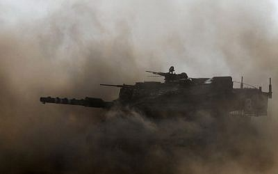 An IDF (Israeli Defense Forces) Merkava tank drives near the Israeli border with Gaza on July 24, 2014. (Photo credit: Miriam Alster/FLASH90)