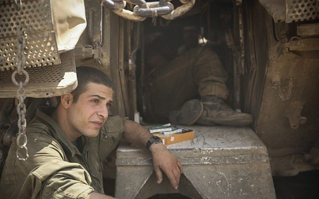 An Israeli soldier rests a moment outside his tank on Friday in a staging area by the Gaza Strip. (Hadas Parush/FLASH90)