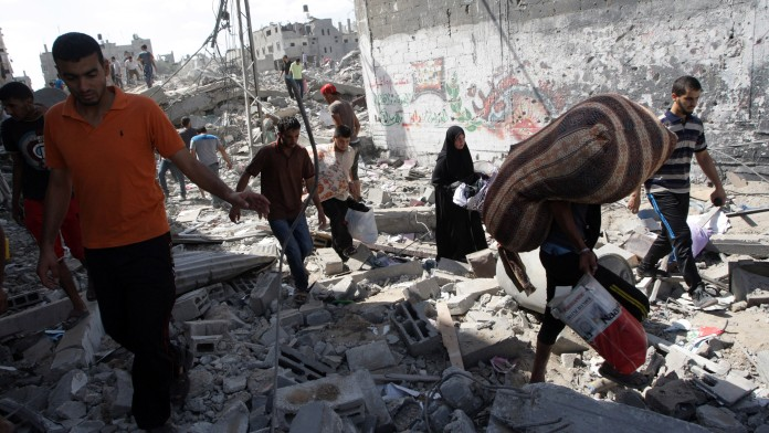 Palestinians inspect the rubble of destroyed houses in the Shejayia neighborhood, which witnesses said was heavily hit by Israeli shelling and air strikes during an Israeli offensive, on Gaza City July 26, 2014. (Photo credit: Abed Rahim Khatib/Flash90)