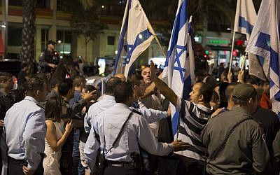 Right-wing Israelis wave the Israeli flag during a demonstration in Rabin square in Tel Aviv, as they rally in support of Israel's offensive in the Gaza Strip ,July 26, 2014. (photo credit: Danielle Shitrit/FLASH90)
