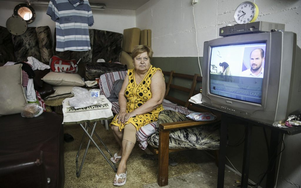 Olga, an immigrant from the former USSR, watches the news in the bomb shelter she has made into her temporary home, in Ashkelon, Southern Israel, on July 30, 2014 (photo credit: Hadas Parush/Flash90)