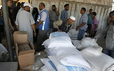 Palestinians receive aid at a United Nations distribution center (UNRWA) in the Rafah refugee camp, southern Gaza Strip on July 31, 2014 (photo credit: Abed Rahim Khatib/Flash90)