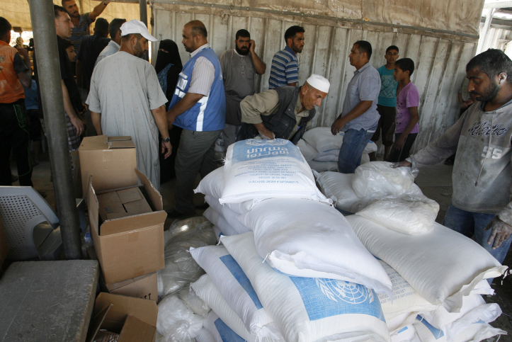 Palestinians receive their monthly food aid at a United Nations distribution center (UNRWA) in the Rafah refugee camp, southern Gaza Strip on July 31, 2014 (photo credit: Abed Rahim Khatib/Flash90)