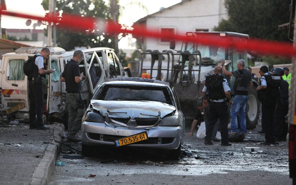 Israeli rescue personnel at the scene where a rocket fired from Gaza hit near a residential building in Kiryat Gat, moderately injuring one person and lightly wounding two more, Thursday, July 31, 2014 (photo credit: Yaakov Naumi/FLASH90)