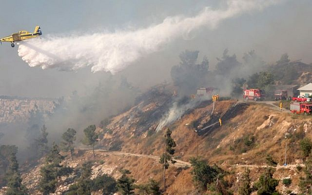 Israeli firefighter airplanes try to extinguish a large fire raging in the hills outside Jerusalem, causing residents in the area to evacuate their homes, on July 2, 2014. (photo credit: Flash90)