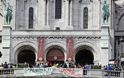 "Pro-Palestinian demonstrators hold banners reading: ""Palestine will live"" and ""Israel assassins,"" in front of the Sacre Coeur basilica at Montmartre in Paris, Saturday July 19, 2014. (photo credit: AP Photo/Remy de la Mauviniere)"