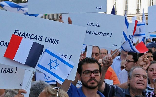 Demonstrators hold Israeli and French flags and placards reading 'French and All United Against Terrorism' during a gathering in front of the Israeli Embassy in Paris, France, Thursday, July 31, 2014. (AP Photo/Francois Mori )