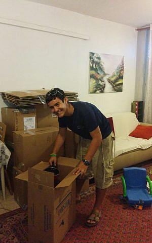 Tzvi Abbo helps the wife of a reserve soldier on duty pack up their house for their planned move up north (Courtesy Tzvi Abbo)